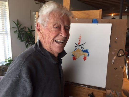 Tubby Raymond with his painting of Dick the Blue Hen, which appeared on all the senior portraits he painted of Delaware football players.