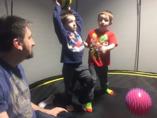John Sutton watches his twin sons, Justin, 4, and Nick, 4, play on the trampoline