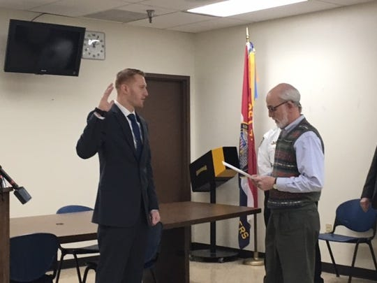 Bradley Gallik was sworn in as a new probationary police officer with the Mansfield Police Department on Friday. Aadministering the oath is Dave Remy, human resources director for the city.