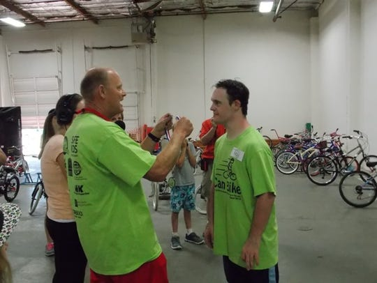 Troy Drake receives a medal from iCan Bike Camp volunteer