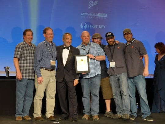 Odell Brewing Co. accepts a World Beer Cup gold medal from Charlie Papazian.