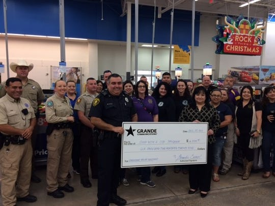 Grande Cares presented a check to the Shop with a Cop program.