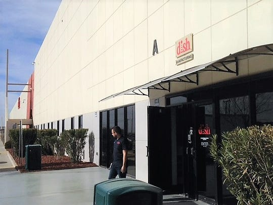 A person Friday leaves the manufacturing division entrance at the Dish Network facility in East El Paso.