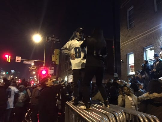 Eagles fans gyrate to hip-hop music on a stack of metal gates in South Philly.
