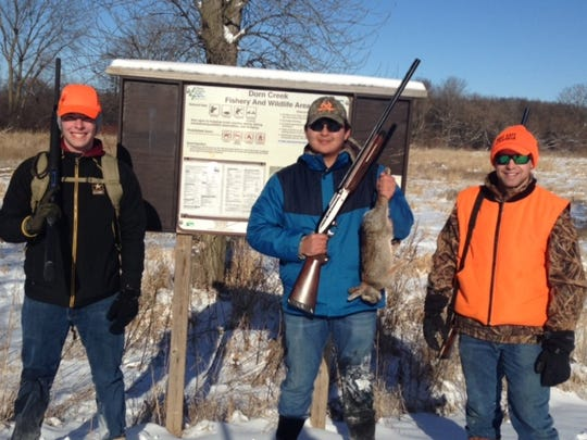 Dustin Li, center, holds a cottontail rabbit he shot while hunting with Lucas Allen (left) and Lucas Olson during a Learn to Hunt for Food program. Olson mentored Allen and Li on the outing; all men are from Madison.