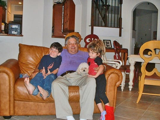 This 2003 photo provided by Merri Novell shows her father Charles Cohen, center, sitting with his grandchildren Carly Novell, right, and Alex Novell, left, at Merri Novell's home in Parkland, Fla. Carly Novell, a student who survived the Florida high school shooting on Wednesday, Feb. 14, 2018, tweeted photos Thursday of Cohen, her late grandfather, saying she hid in a closet to escape just like Cohen did during a 1949 shooting rampage in New Jersey, when Cohen was 12. Cohen's mother, father, grandmother and 10 other adults and children were gunned down by 28-year-old war veteran Howard Unruh on Sept. 6, 1949, in Camden, N.J. (Merri Novell via AP)