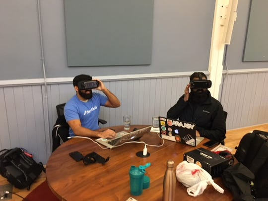 Renji Bijoy, left, founder and CEO of Immersed, tests out his company's new virtual reality headset at startup incubator, Cintrifuse, in Over-the-Rhine.