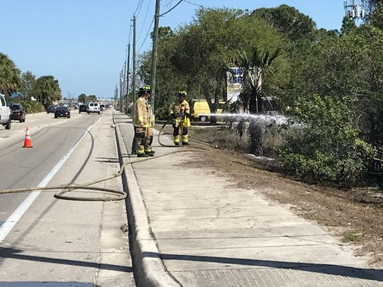 San Carlos Park Fire Department firefighters work on a brush fire neat to the 7/Eleven on Alico Road at Lee Road Monday afternoon.