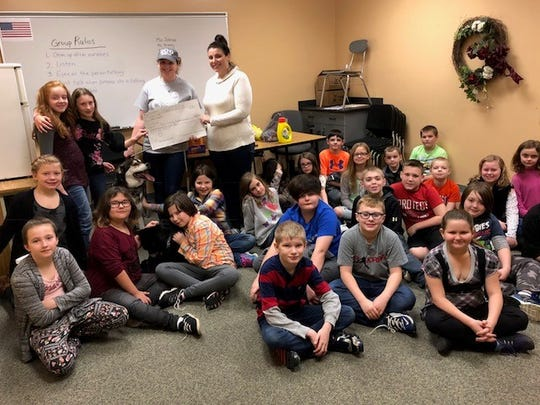 Students in Lynn Cowman's fourth-grade class at Paint Valley Elementary present a large check they created as part of a real $257.50 donation to the Ross County Humane Society they made from a project they created.