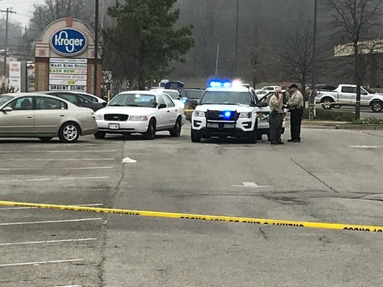 Shelby County Sheriff's deputies investigate the are in a parking lot where one of two victims was stabbed Sunday