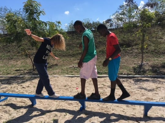 Jill Engel walks the balance beam with two Haitian children during a field trip.