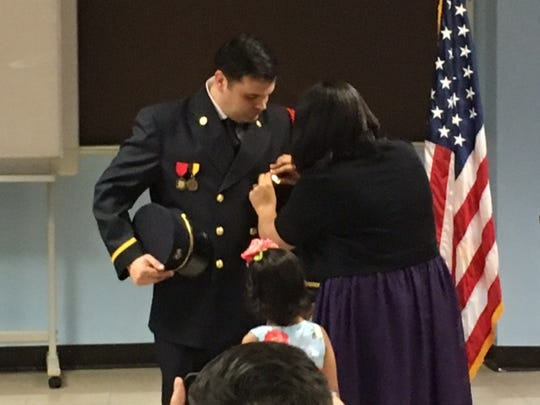 Dan Crow was promoted to lieutenant at Mansfield Fire Station No. 1 Tuesday afternoon. Here his wife Carla, pins on his badge, as their daughter Isabelle joins them.