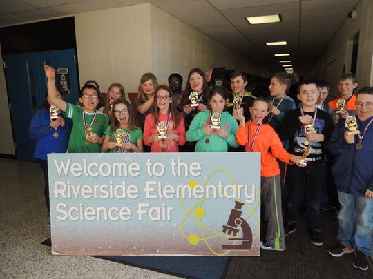 Riverside Elementary science fair participants show off their trophies and medals.