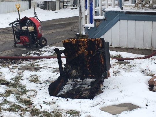 A burned chair sits in front of a mobile home where