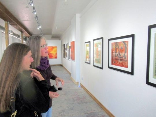 Two patrons view the artwork in Limina Art Gallery