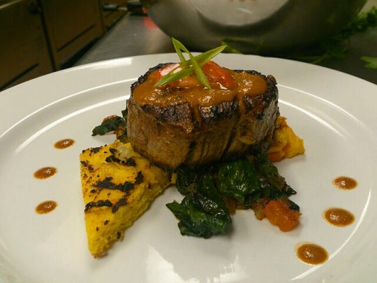 A filet served with spinach and grilled polenta is