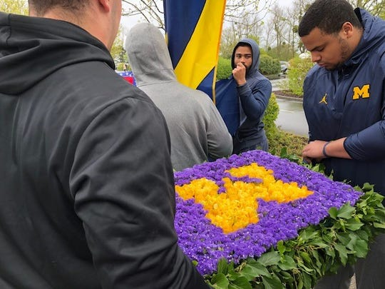 """Michigan football players carry a flower arrangement that was placed Sunday at the base of """"Spirit of American Youth Rising from the Waves"""" sculpture at the American Cemetery in Normandy, France."""