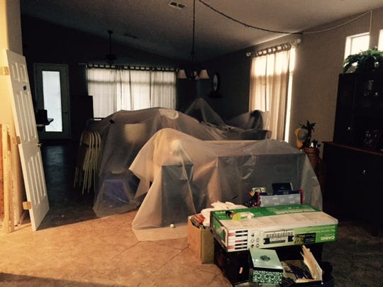 Plastic sheets in the living room cover furniture several