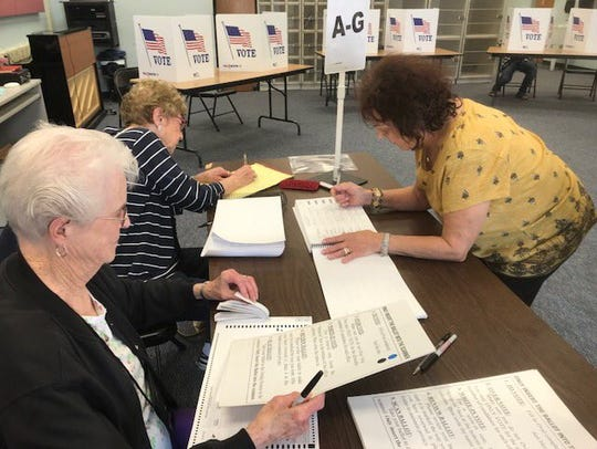 Mary DiLorenzo of Highland signs in to vote at Highland High School on Tuesday. Poll workers Patricia Winchell, left, and Angela Grieco assist her.