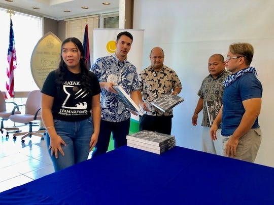 Guam Visitors Bureau President Jim Denight, second from left, on Wednesday leads the donation to public schools of 50 copies of Pulitzer Prize-winning photographer Manny Crisostomo's book which captures stunning images from the 2016 Festival of the Pacific Arts that Guam hosted.