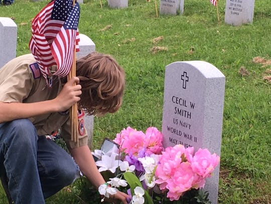 Boy Scout Jackson West, 16, of Troop 116, posts a flag at a veteran's headstone in the Veterans Honor Grounds at Mansfield Cemetery on Saturday morning.