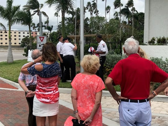 Kevin Boyd, commander of American Legion Post 38 in Fort Myers, and post members David Mulholland and Daniel Pfeifer, prepare to raise a new flag at Campo Felice in downtown Fort Myers, while residents of the retirement living facility pay their respects.