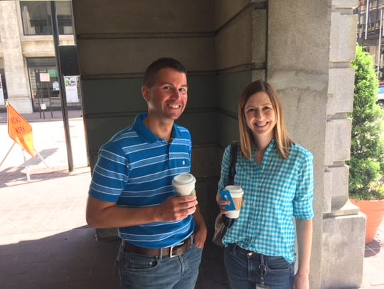 Office workers Michael Fischer, left, and Carrie Jones outside the Starbucks at Fourth and Vine streets Downtown.