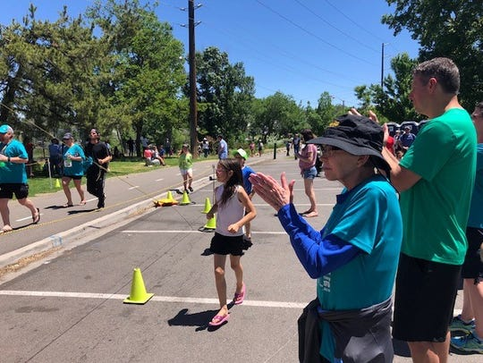 Lolly Hedeen (black hat) encourages runners in the