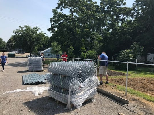 Lowe's employees and community volunteers work to build a garden fence at the Christian Community Outreach Center on Thursday, June 7, 2018.