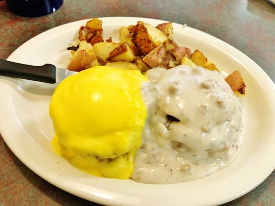 Two different Eggs Benedicts at Grandpa's Diner in Port St. Lucie. One Egg Benedict (left) was a poached egg with ham on an English Muffin covered with Hollandaise sauce. The other was a Sausage Benedict with a poached egg with sausage patty on a biscuit covered with sausage gravy and served with home fries.