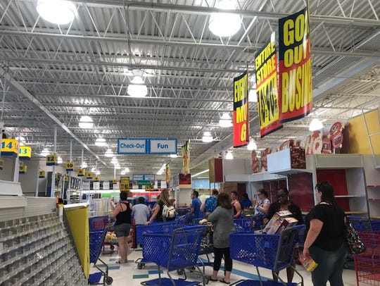Customers wait in line to purchase clearance items