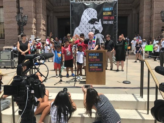 Retired Methodist Bishop Joel Martinez of San Antonio leads children in prayer and the Families Belong Together rally in Austin on Saturday.