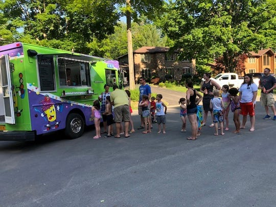 The Yummies food truck serves a group of excited young customers.