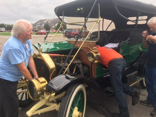 Chuck Sharpe of Michigan, at left, Wednesday discovered his 1910 Buick had a mechanical problem before he left The Comfort Inn South near Bellville for a day trip with the Midwest Brass & Gas Car Club. A retired newpaper man, Sharpe said the car hadn't been out of the garage for two years and only has about 10,000 miles on it.