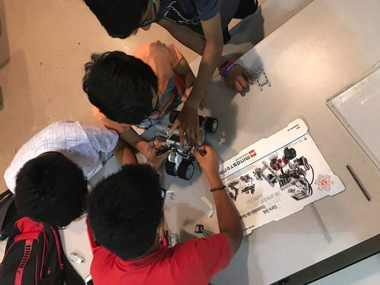 Rise of the Robots students collaborate to prepare their robot for a tug-of-war competition.
