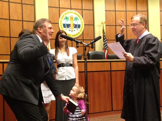 Steve Teuber being sworn in to the Lee County School Board as his granddaughter holds the Bible.