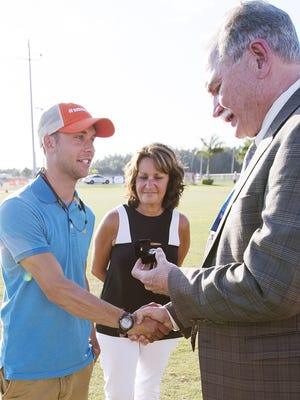 Adam Sommer, left, and Susan Sommer, center, accept the  FHSAA Honor of Distinction award on behalf of the late Jeff Sommer on Thursday, May 19, 2016.