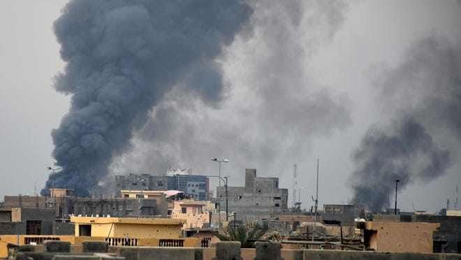 Smoke rises from Islamic State positions following a U.S.-led coalition airstrike as Iraqi Security forces advance their position in downtown Ramadi, 70 miles  west of Baghdad, Iraq on Thursday.