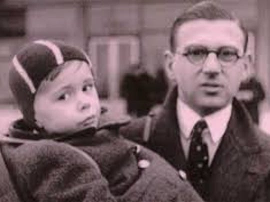 Stockbroker Nicholas Winton holds a young boy during