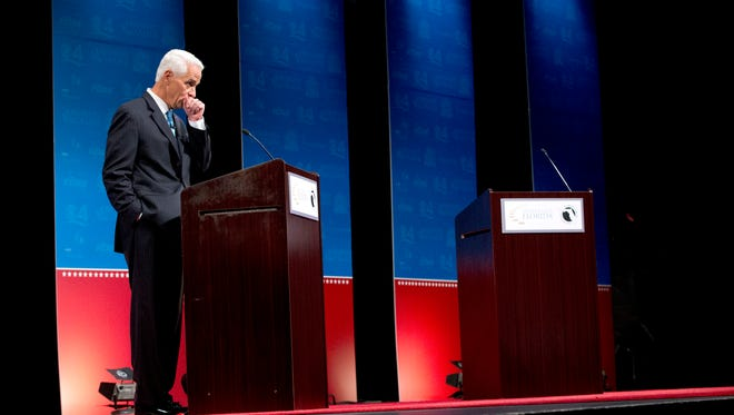 Democratic challenger, former Republican Gov. Charlie Crist stands at his podium as he waits for Florida Republican Gov. Rick Scott during a debate, Wednesday, Oct. 15, 2014 in Davie, Fla. It was sponsored by the Florida Press Association and Leadership Florida. (AP Photo/Wilfredo Lee)