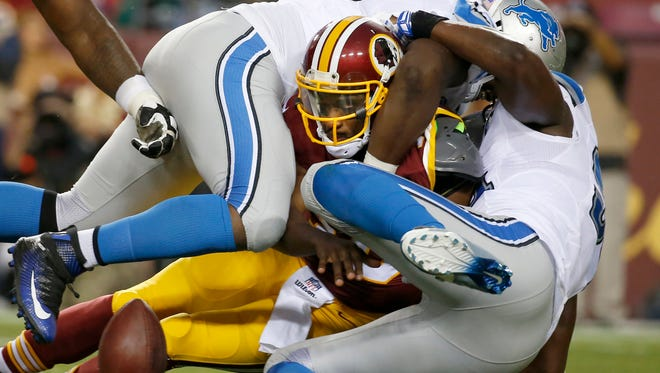Redskins quarterback Robert Griffin III fumbles the ball as he's sacked by Lions defensive end Tyrunn Walker, top, and defensive end Ezekiel Ansah, right, during the first half Thursday in Landover, Md.