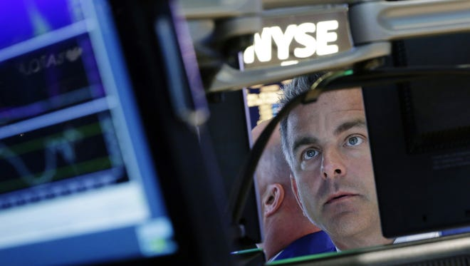 In this Sept. 18, 2013, file photo, specialist Christopher Culhane works at his post on the floor of the New York Stock Exchange.