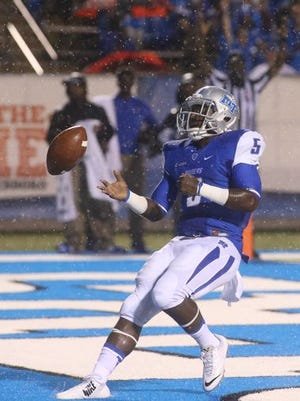 MTSU running back Jeremiah Bryson flips the ball to the official after scoring one of his two TDs in the opener.