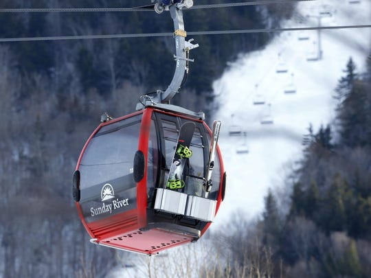 A snowboarder and skier ride the Chondola ski lift at the Sunday River ski resort in Newry, Maine. Sunday River is already open seven days a week for the season. An Oct. 19 opening earlier this fall was its third earliest opening in its 56-year history.