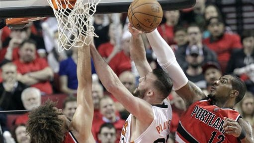 Portland Trail Blazers forward LaMarcus Aldridge, right, blocks a shot by Phoenix Suns center Miles Plumlee, middle, as Trail Blazers center Robin Lopez defends during the second half of an NBA basketball game in Portland, Ore., Thursday, Feb. 5, 2015.  Aldridge scored 19 points, pulled in 13 rebounds and blocked two shots as the Trail Blazers won 108-87.
