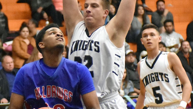 Las Cruces High's R.J. Brown looks to go up for a shot as Onate's Noah Williams puts on the pressure on defense on Friday night at Onate High School.