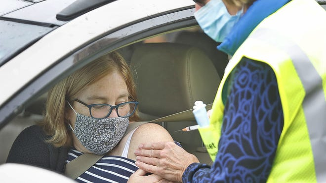 Mary McKelvey gets a flu shot from Nurse Mary Whitley at a drive-thru flu shot clinic in Cohasset on Wednesday, Oct. 21, 2020. Marshfield's COVID-19 mass vaccinaton site opens Monday, Feb. 8. Greg Derr/ The Patriot Ledger