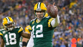 Green Bay Packers quarterback Aaron Rodgers (12) celebrates after scoring a touchdown during the fourth quarter against the Detroit Lions at Lambeau Field.