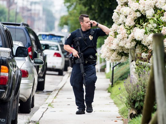 A York City police officer walks near the scene of a police standoff in an alley near Spring Avenue in Hanover Borough on Monday, August 7, 2017.