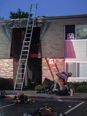 Firefighters work at the scene of a fire at Ashford Cove apartment complex on Miracle Mile Drive in Anderson on Tuesday night.